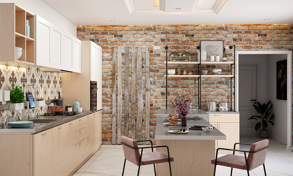 An exposed brick wall and stainless steel top in kitchen island with overhead cabinets and bottom drawers look rustic.