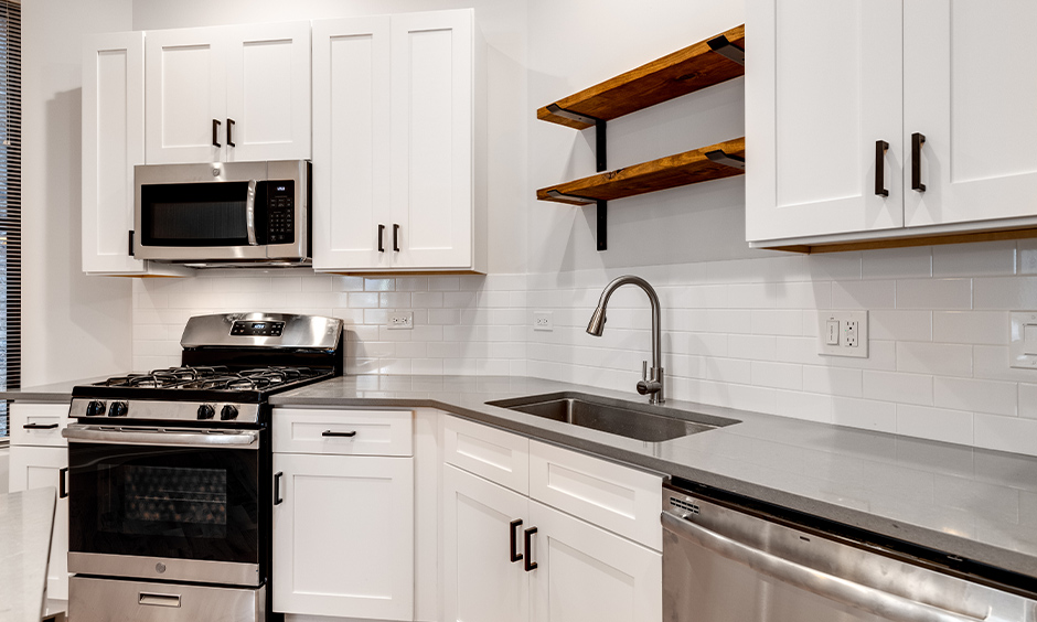 All-white kitchen with the countertop in stainless steel kitchen island inspired from the '90s looks impressive.