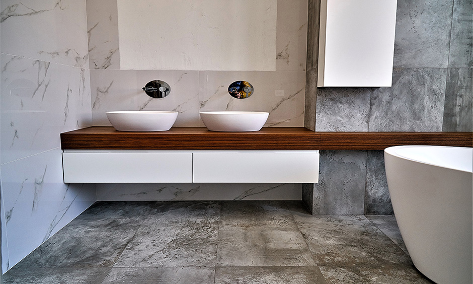 Wooden floating bathroom countertop with two sinks in a modern bathroom look aesthetic.