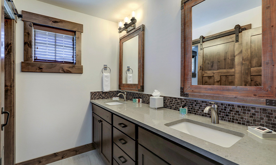 Light Grey quartz bathroom double sink countertop with vanity cabinets and barn-style doors tie the whole farmhouse look.