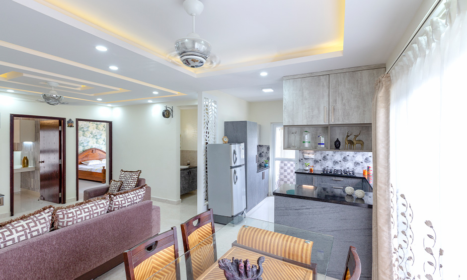 Apartment small u-shaped open kitchen design with living room in India looks more spacious kitchen.