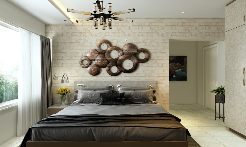 Elegant bedroom designed with a stone wall cladding tiles in a light hue enhances the look of space.