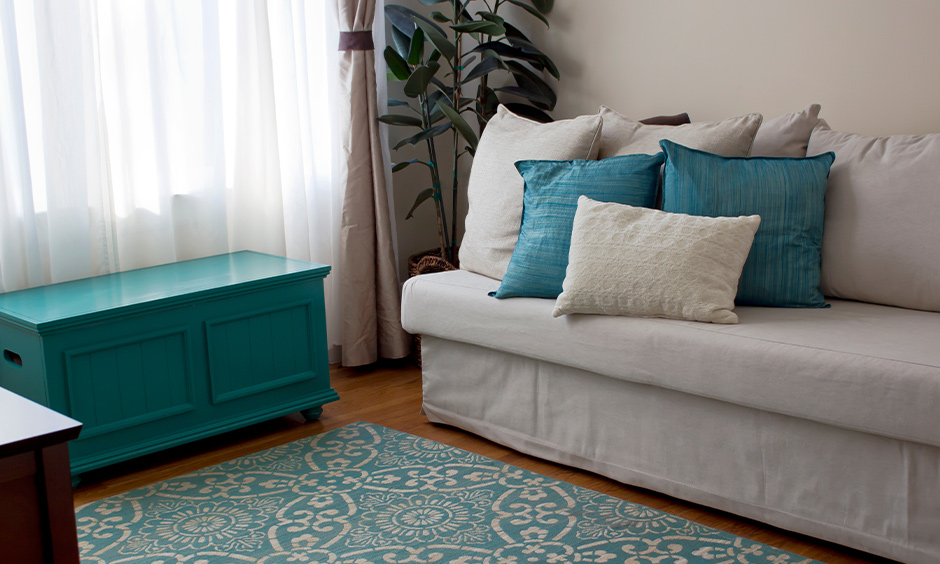Living room with aqua blue coloured cabinet and cushions looks calming, aqua paint color for living room.