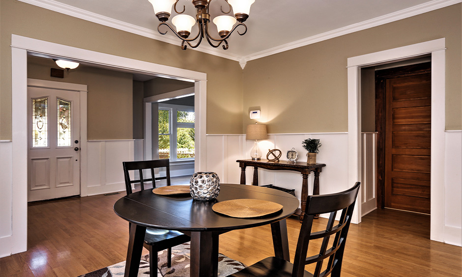 Best color for dining table, dining room with a round wooden table and two chairs in black colour looks bold.
