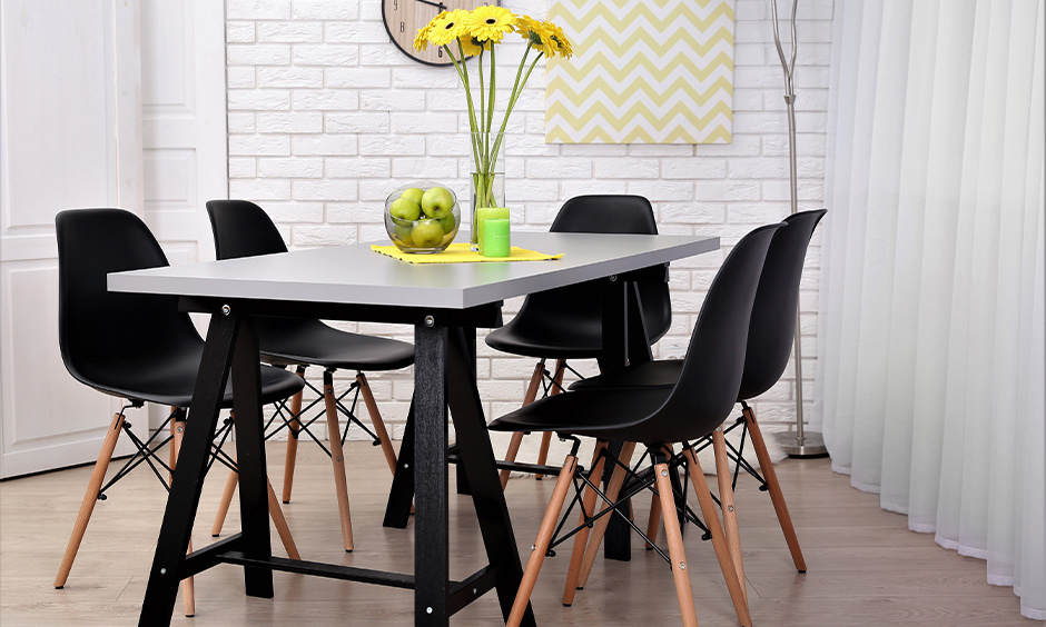 Modern colourful dining table in silver and black with chairs looks chic.