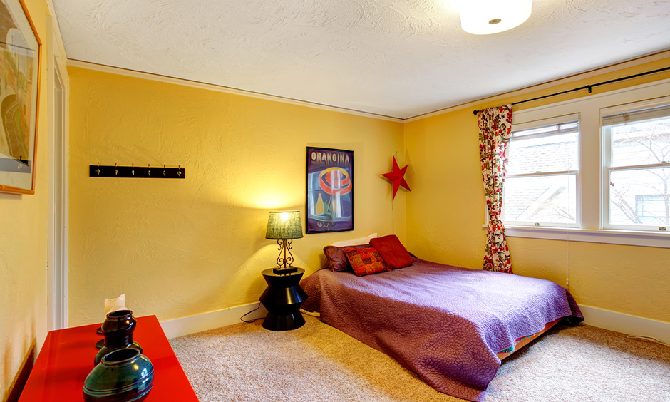 Bold printed curtains for yellow walls gives your bedroom look bright and feel cosy