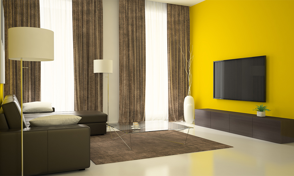Bright yellow walls with grey and beige toned curtain drapes for hotel room vibes in your home