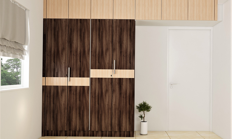 Light and dark brown wooden almirah colour combination lends a warm vibe to the bedroom.
