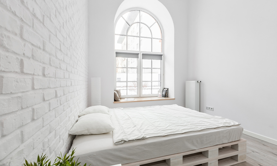 All-white simple bedroom window design in an arched shape with seating option brings elegance to the area.