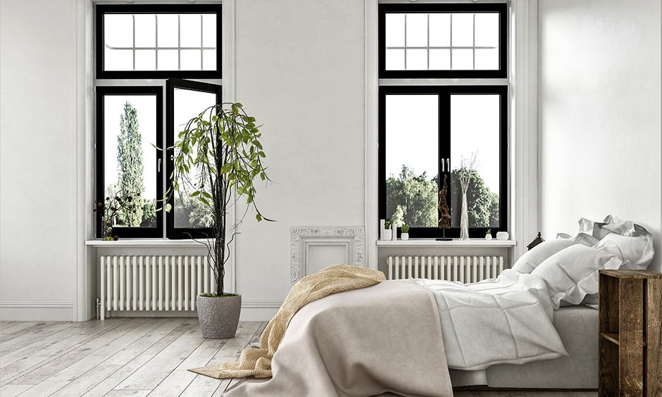 White bedroom design with two windows with black frame adds a pop of colour to the area.