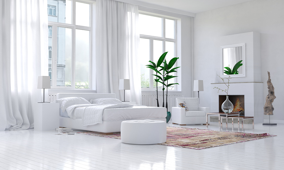 Large windows behind the bed and armchair in an all-white bedroom look stunning, Window design for bedroom Indian.
