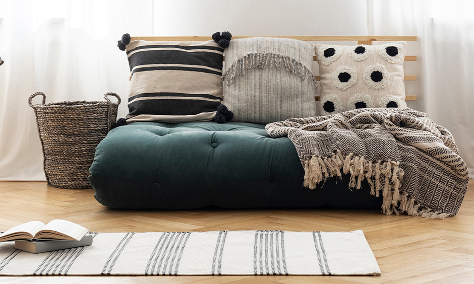 Patterned cushion paired with grey rugs elevates the area's look and comfort, floor cushion seating idea.