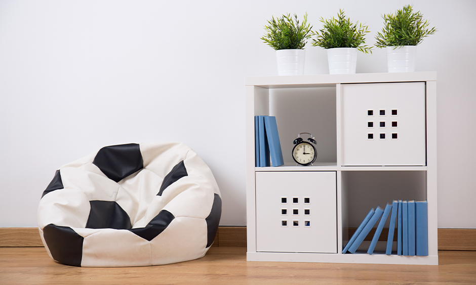Floor seating idea, a soccer-themed bean bag in the living room next to the bookshelf evaluates the look.