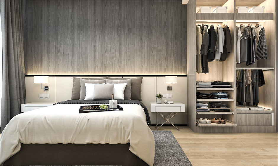 Grey open wardrobe designed with three hanging rods and pull-out shelves, bedroom wardrobe inside design for men.