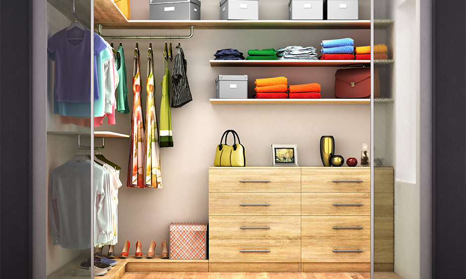 Small walk-in wardrobe inside design for ladies with a set of drawers, hanging rod and shelves.