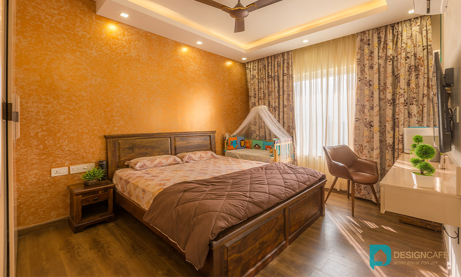 Master bedroom in an earthy tone designed with tv unit is stunning and best interior design for 2bhk flat in bhoganhalli.