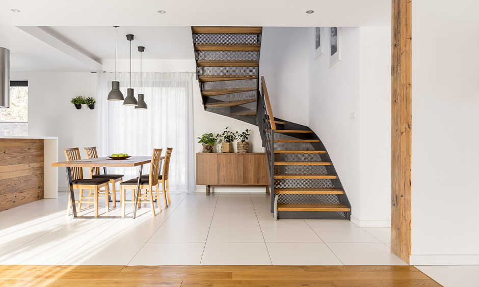 Modern open staircase design with mesh and wood in the white dining area creates old-world glamour.