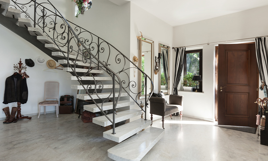 Open staircase designed with iron and marble in the vintage style home brings a modern edge.