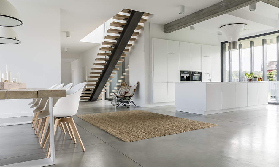 Wooden slats open staircase, minimalistic white kitchen cum dining area with open staircase adds an airy vibe.