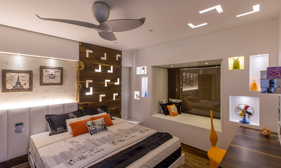 Tumkur road interior designer, white bedroom cum study area with ceiling lights and wooden flooring creates a luxury look.