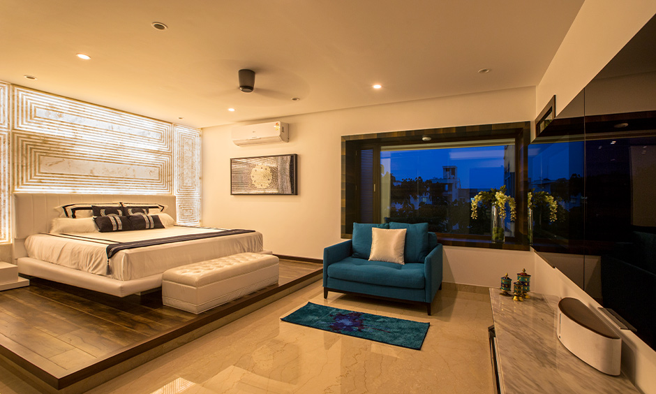 Master bedroom with a white bed, blue sofa and wall lighting behind the headboard, 3bhk independent house interior design.