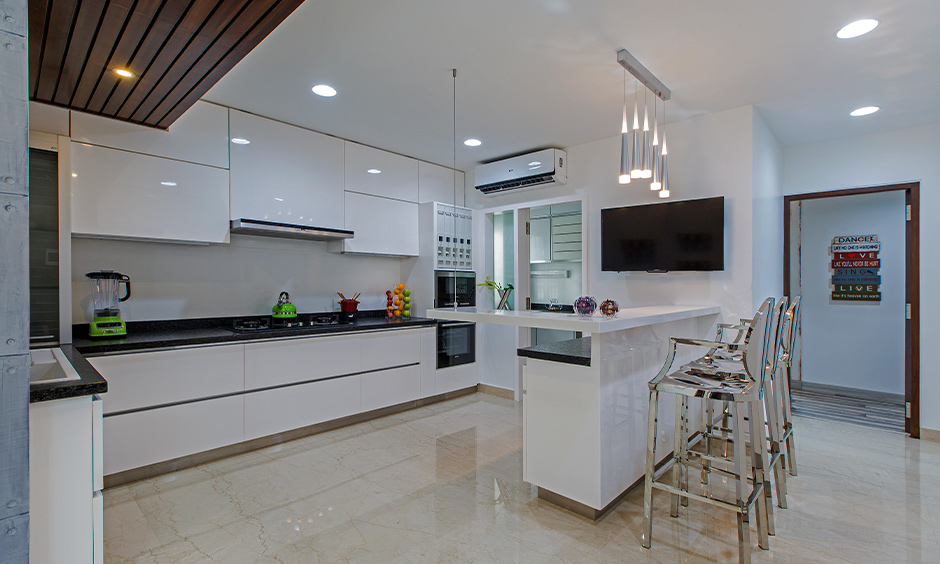 White minimalist kitchen designed in 3BHK independent house in Tumkur Road, Bengaluru with breakfast counter and steel chairs look elegant.