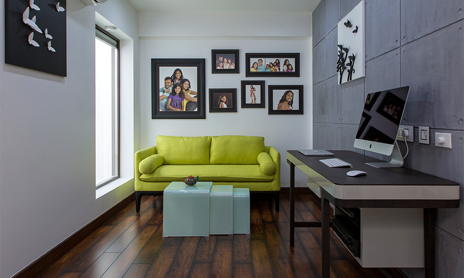 Study room designed with a yellow couch, desk and wooden flooring in Tumkur road home designed by design cafe.