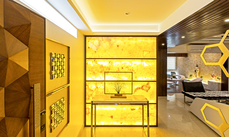 Tumkur road home designed with a foyer area with a yellow alabaster sheet with lights at the back creates a warm welcome.