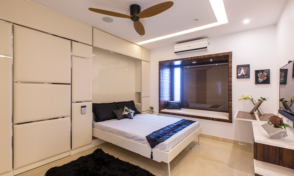 Tumkur road home design, a guest room designed with a murphy bed and tv unit brings elegance and comfort.