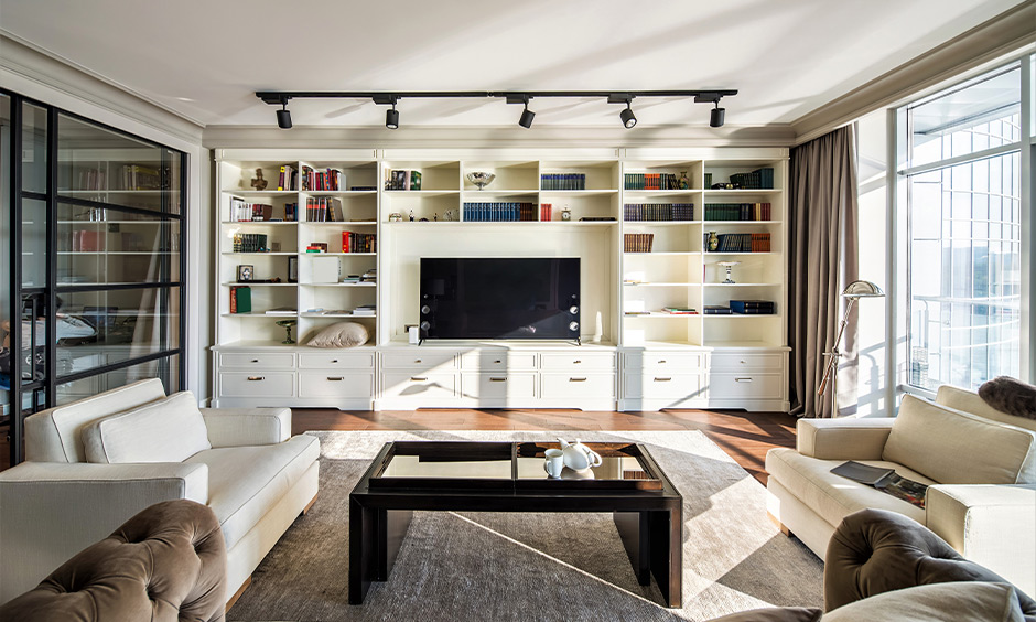 Hall tv furniture designed with cabinets and open shelves stored with equipment and books looks classic.