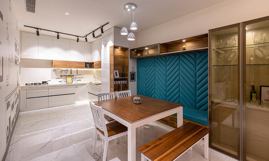 Modern minimalist style white kitchen cum dining area designed by dc interior designer in Whitefield Bangalore.