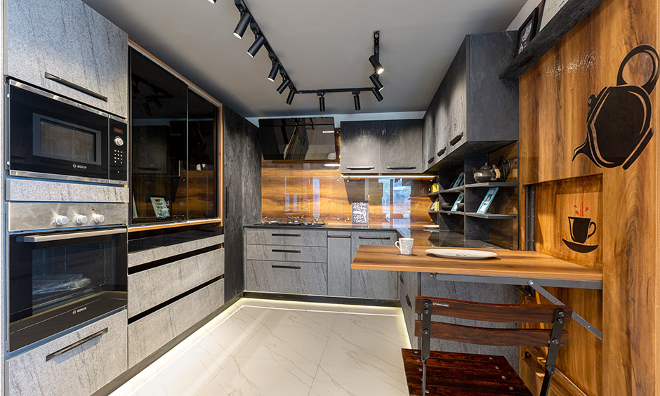 U-shaped kitchen with the tall unit, pantry and folding dining table look warm and designed by Design cafe in Whitefield.