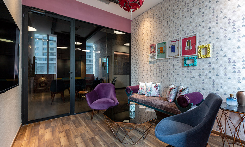 Design cafe interior designer in Whitefield designed kitsch room with unique seating, frames and patterns on the wall.