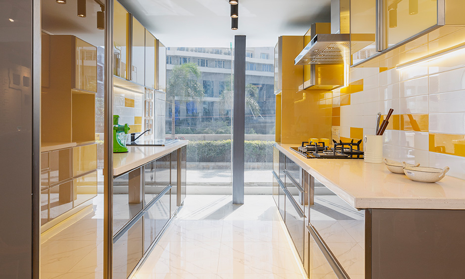 Design cafe interior designer in Whitefield designed parallel modern bold kitchen with cabinets in yellow and brown shade.