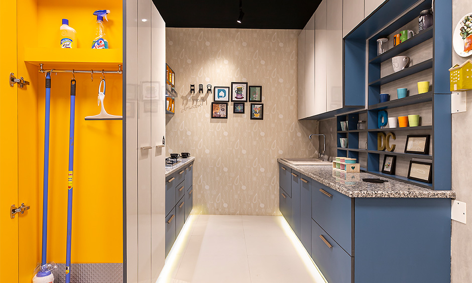 Design cafe experience centre, Parallel kitchen with blue and white laminate cabinets and janitor unit brings joyful.