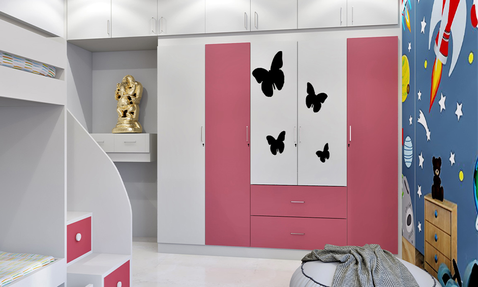 White and pink coloured wardrobe door decorated with animated stickers in the kids' bedroom, wardrobe decoration DIY.