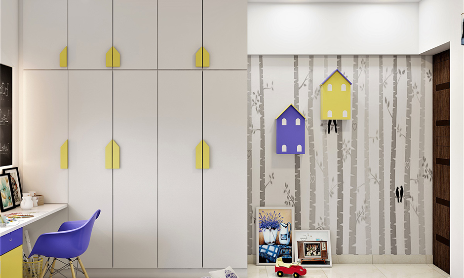 White wardrobe door knobs decorated in yellow house shape is how to decorate the wardrobe in kid bedroom.