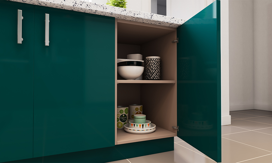 Green coloured base unit with cups, bowl, and plates placed inside it, Kitchen storage idea in India.