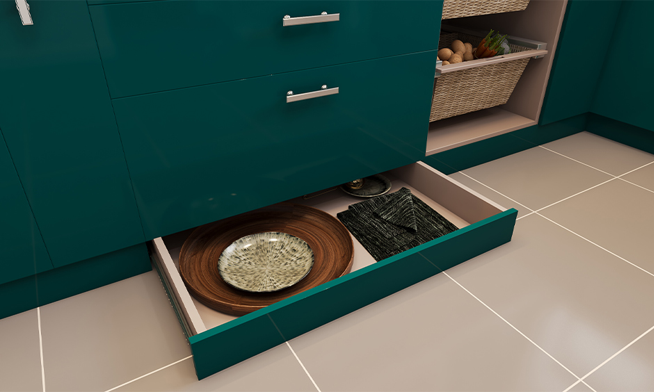 Best kitchen storage designed in a green laminated skirting drawer under the base unit stored with cleaning cloths and paper bags.