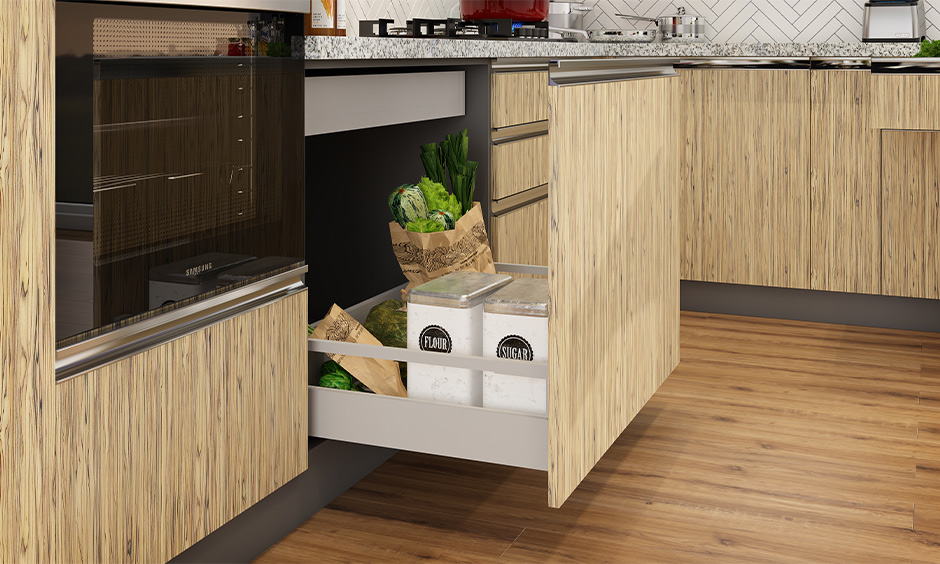 Kitchen cupboard storage solutions with green coloured tandem drawer with sacks of rice, pulses, and flours stored in it.