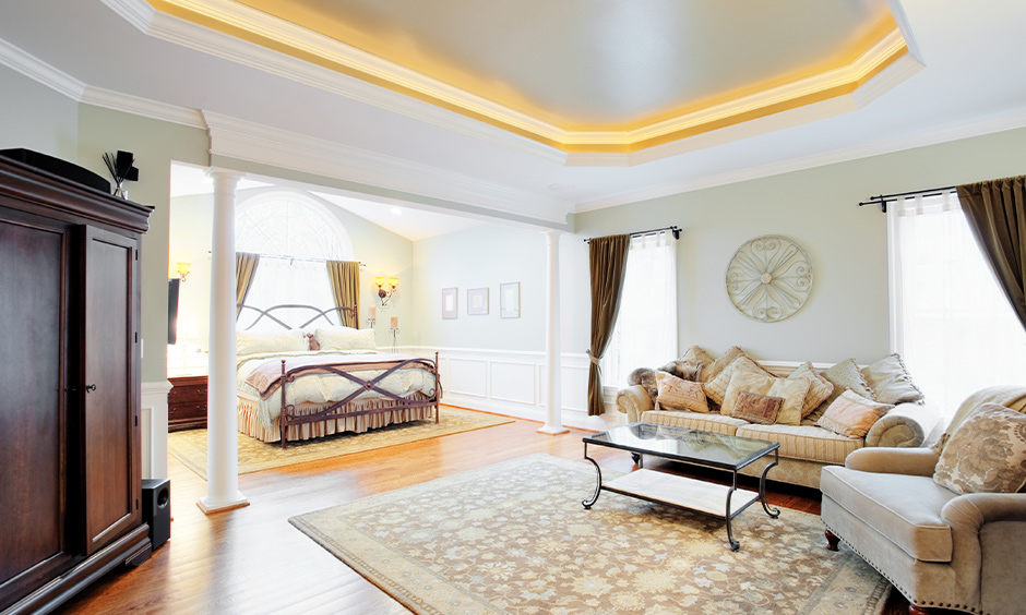 The contemporary living room has led strip light coving in the false ceiling corners.