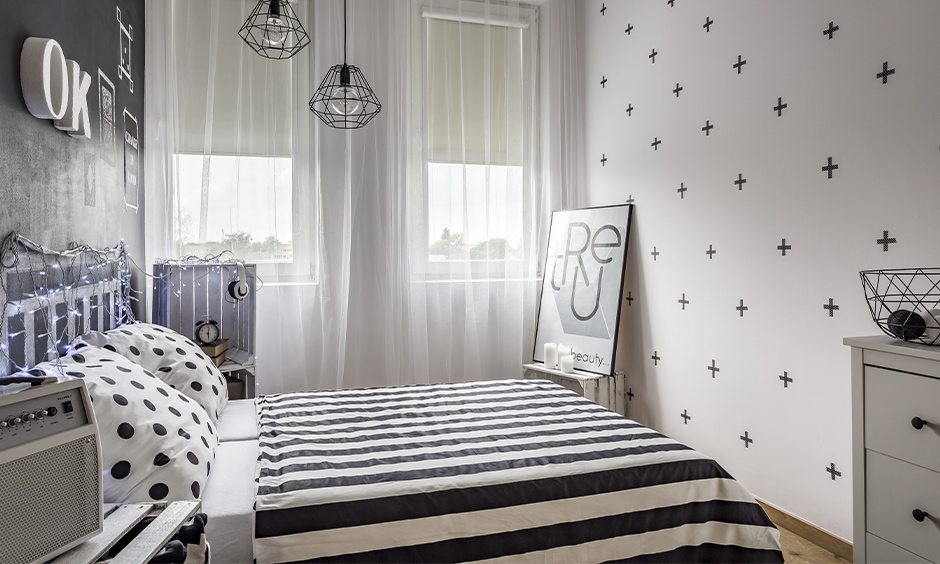 Two small bedroom lighting designed in geometric shape hanging from the ceiling look modern.