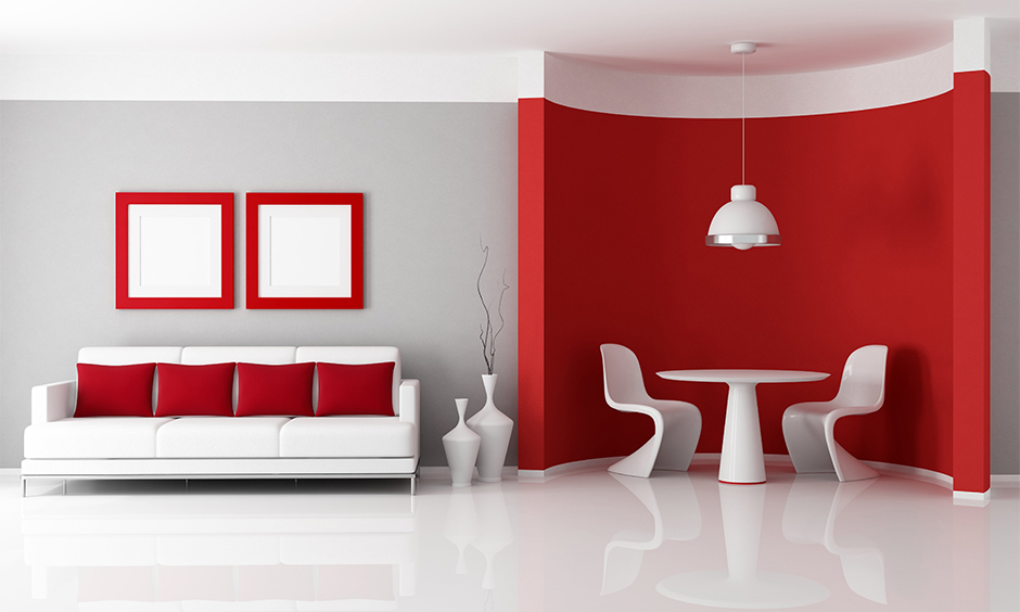 Half grey and half red wall living room with white round table and sofa emphasise the red in the room.