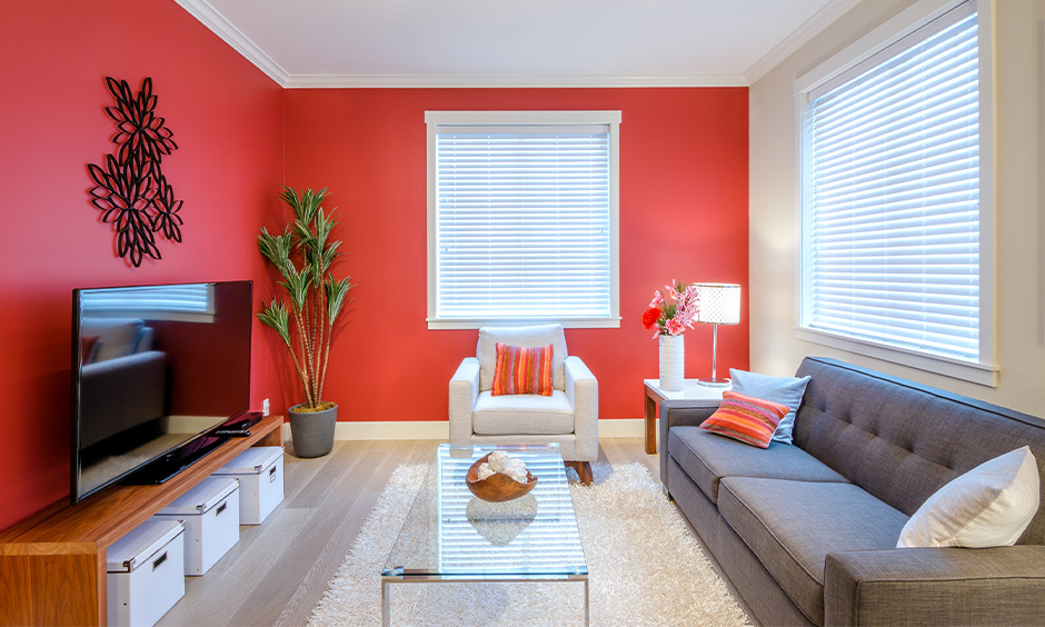 Red and white living room walls with minimal design create a vibrant and cheerful atmosphere.