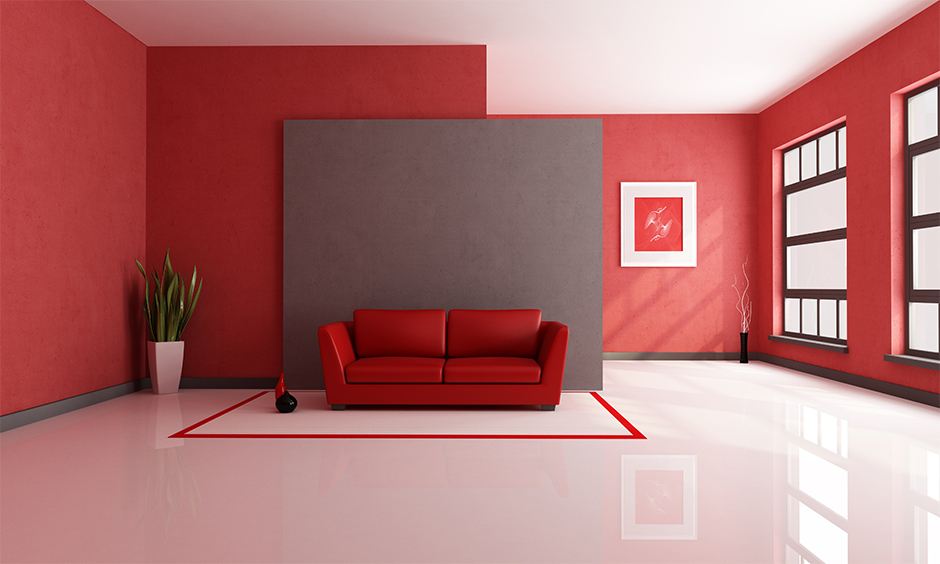 Red living room with red sofa in front of a grey background looks minimalist.