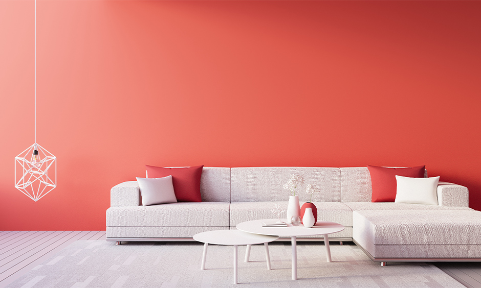 Red wall in the living room with minimal design adds boldness to space.