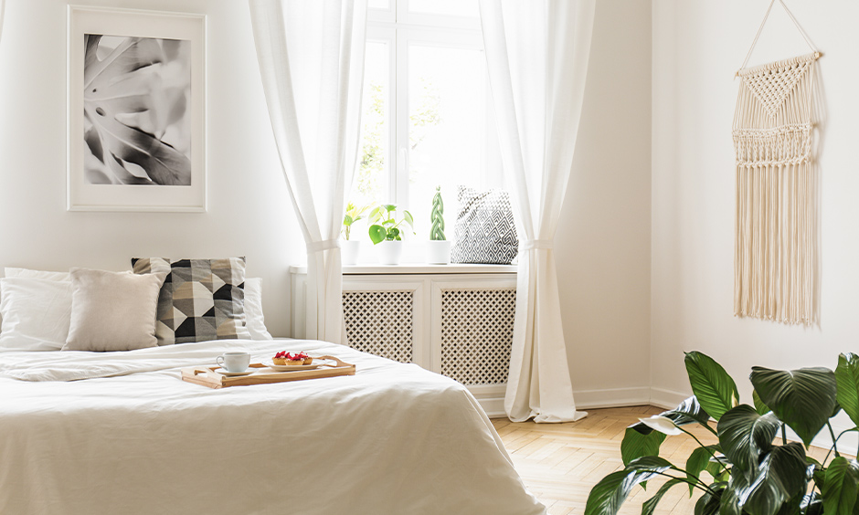 Simple white bedroom curtains in flowy texture for a small window are charming.