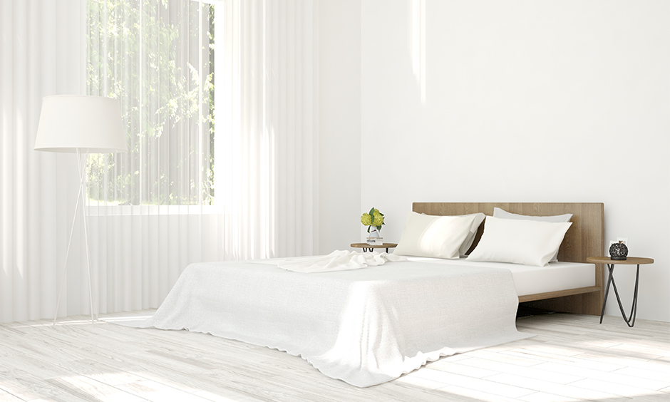 Two types of white curtains for white walls in a bedroom with different textures look classy.