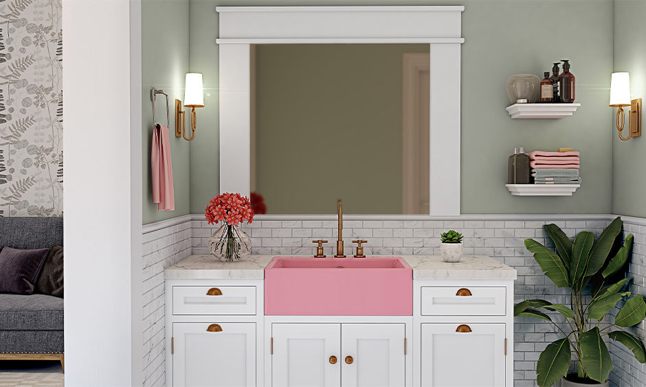 Plush pink colour wash basin with white storage cabinet in the bathroom stands out in a minimalistic way.