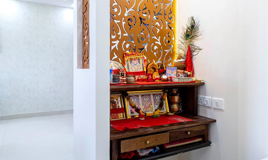 Best budget interior designer in Marathahalli Bangalore designed traditional pooja unit with storage and laser-cut panel.
